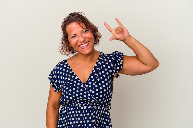 Middle age latin woman isolated on white background showing a horns gesture as a revolution concept.