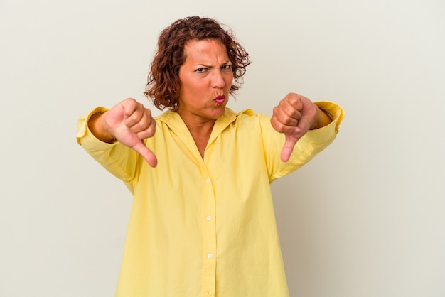 Middle age latin woman isolated on white background showing thumb down and expressing dislike.