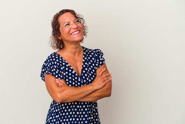 Middle age latin woman isolated on white background smiling confident with crossed arms.