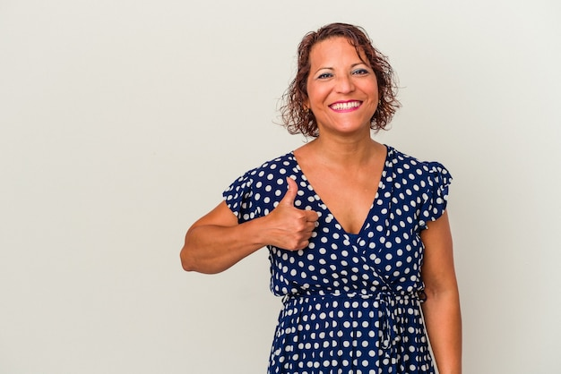 Middle age latin woman isolated on white background smiling and raising thumb up