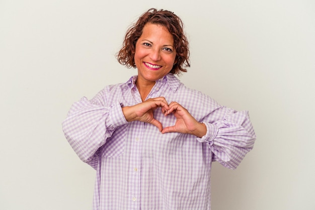 Middle age latin woman isolated on white background smiling and showing a heart shape with hands.