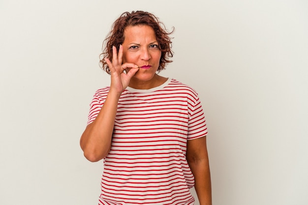 Middle age latin woman isolated on white background with fingers on lips keeping a secret.