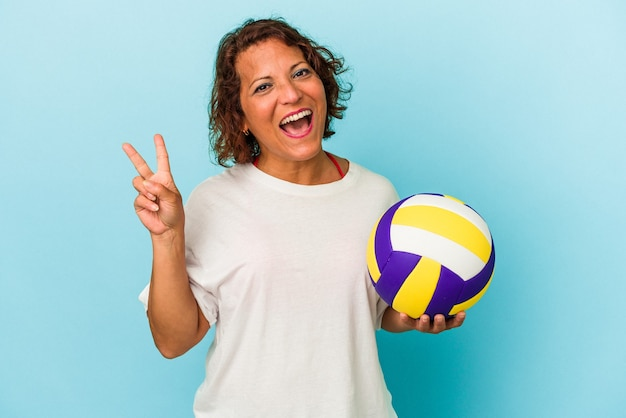 Middle age latin woman playing volleyball isolated on blue background joyful and carefree showing a peace symbol with fingers.