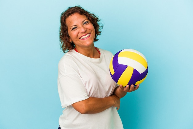 Middle age latin woman playing volleyball isolated on blue background laughing and having fun.