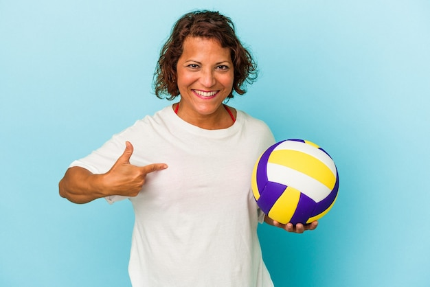 Middle age latin woman playing volleyball isolated on blue background person pointing by hand to a shirt copy space, proud and confident
