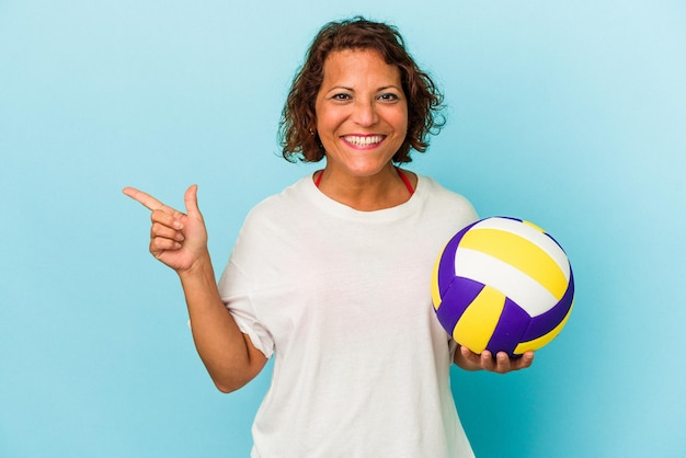 Middle age latin woman playing volleyball isolated on blue background smiling and pointing aside, showing something at blank space.