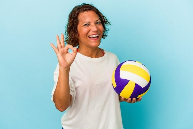 青の背景に分離されたバレーボールをしている中年のラテン女性は、陽気で自信を持って大丈夫なジェスチャーを示しています。