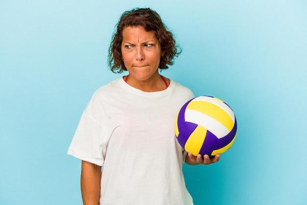 青い背景に分離されたバレーボールをしている中年のラテン女性は混乱し、疑わしく、不安を感じています。