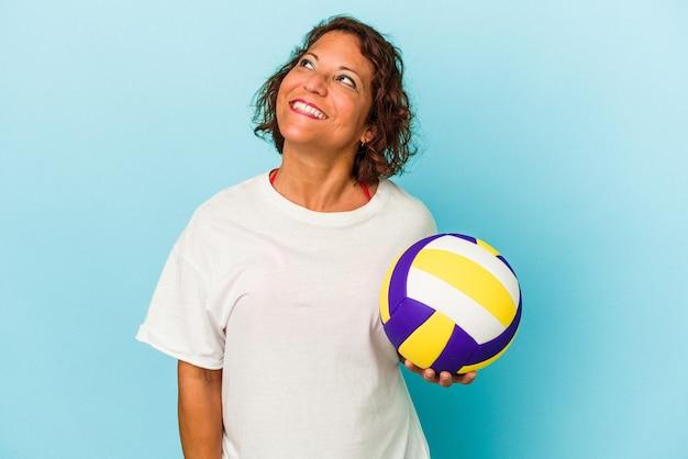 目標と目的を達成することを夢見て青い背景に分離されたバレーボールをしている中年ラテン女性