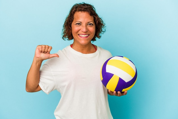 青い背景に分離されたバレーボールをしている中年のラテン女性は、誇りと自信を感じています。