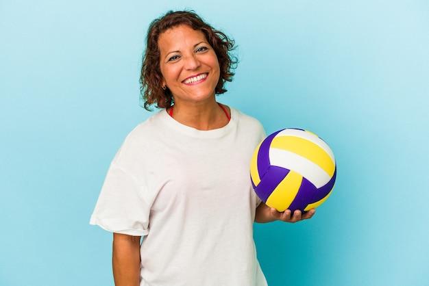 幸せ、笑顔、陽気な青い背景で隔離のバレーボールをしている中年ラテン女性。