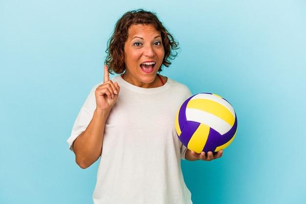 いくつかの素晴らしいアイデア、創造性の概念を持っている青い背景に分離されたバレーボールをしている中年ラテン女性。