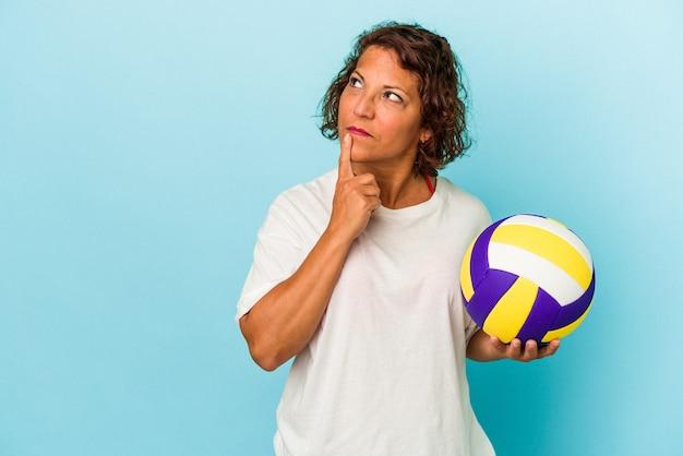 疑わしいと懐疑的な表情で横向きに青い背景に分離されたバレーボールをしている中年ラテン女性。