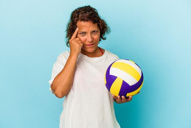 指で寺院を指して、思考、タスクに焦点を当て、青い背景で隔離のバレーボールをしている中年ラテン女性。