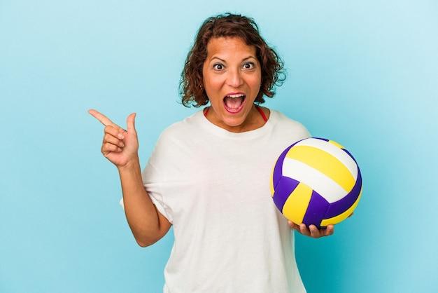 側面を指している青い背景で隔離のバレーボールをしている中年ラテン女性