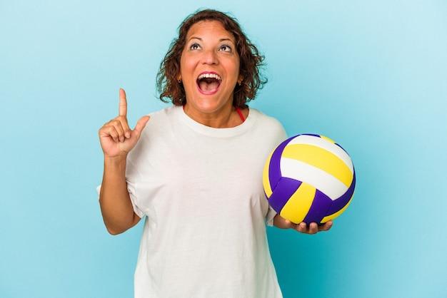 口を開けて逆さまを指している青い背景に分離されたバレーボールをしている中年ラテン女性。
