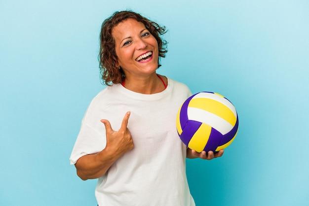 파란색 배경에 격리된 배구를 하는 중년 라틴 여성은 마치 초대하는 것처럼 손가락으로 당신을 가리키고 있습니다.