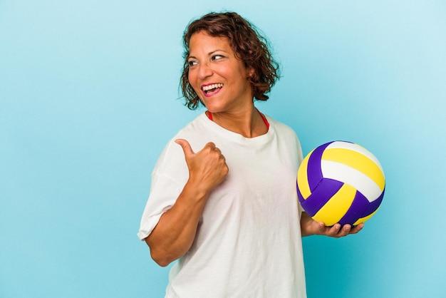 親指の指を離れて、笑ってのんきな青い背景のポイントで隔離のバレーボールをしている中年のラテン女性。