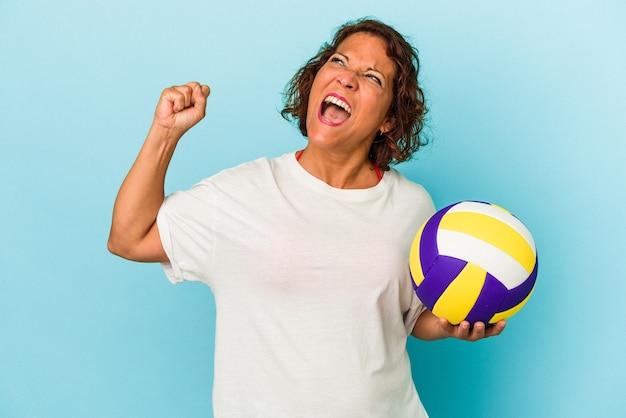 勝利、勝者の概念の後に拳を上げる青い背景に分離されたバレーボールをしている中年ラテン女性。