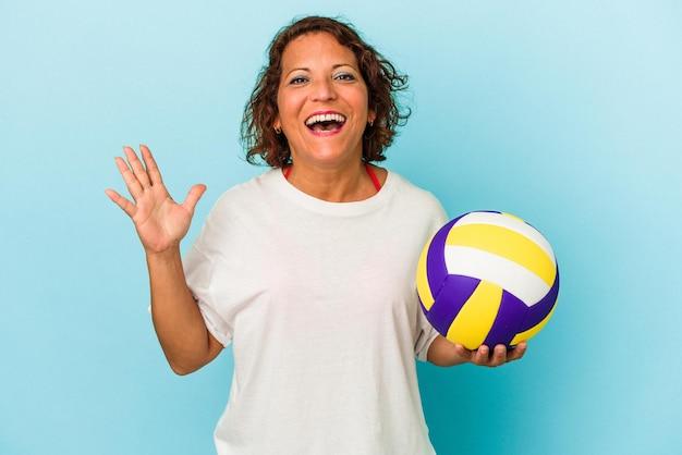 青い背景に分離されたバレーボールをしている中年のラテン女性は、嬉しい驚きを受け取り、興奮し、手を上げます。