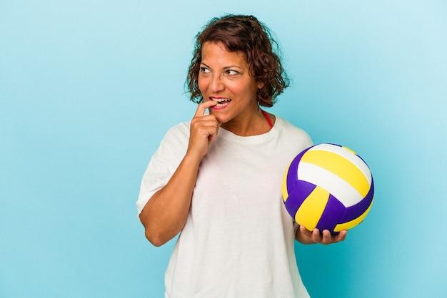 青い背景に分離されたバレーボールをしている中年ラテン女性は、コピースペースを見ている何かについて考えてリラックスしました。