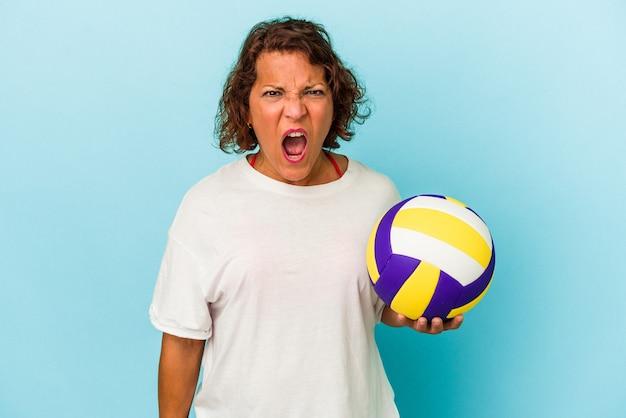非常に怒って攻撃的な叫び声の青い背景に分離されたバレーボールをしている中年ラテン女性。