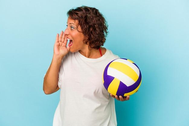 開いた口の近くで叫び、手のひらを保持している青い背景で隔離のバレーボールをしている中年ラテン女性。