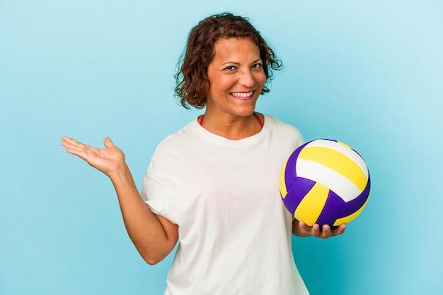 手のひらにコピースペースを示し、腰に別の手を保持している青い背景で隔離のバレーボールをしている中年ラテン女性。