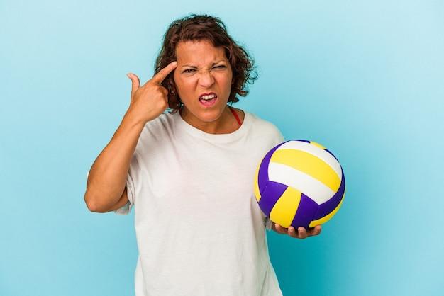 人差し指で失望のジェスチャーを示す青い背景で隔離のバレーボールをしている中年ラテン女性。