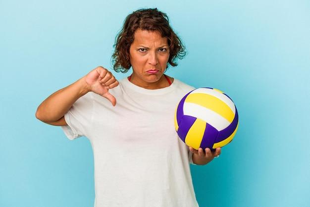 嫌いなジェスチャーを示す青い背景に分離されたバレーボールをしている中年のラテン女性、親指を下に向けます。不一致の概念。