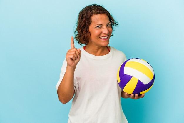 指でナンバーワンを示す青い背景で隔離のバレーボールをしている中年ラテン女性。