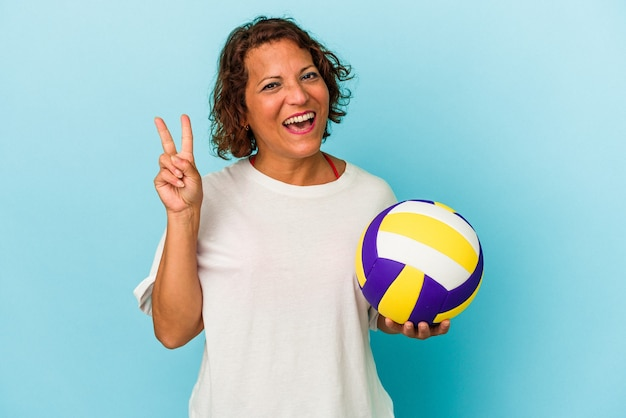 指で2番目を示す青い背景で隔離のバレーボールをしている中年ラテン女性。