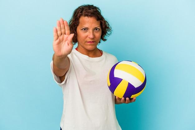 一時停止の標識を示す伸ばした手で立っている青い背景に分離されたバレーボールをしている中年のラテン女性は、あなたを防ぎます。