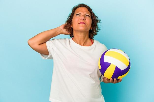 頭の後ろに触れて、考えて、選択をする青い背景に分離されたバレーボールをしている中年ラテン女性。