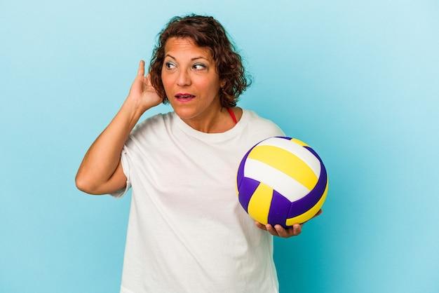ゴシップを聴こうとしている青い背景で隔離のバレーボールをしている中年ラテン女性。