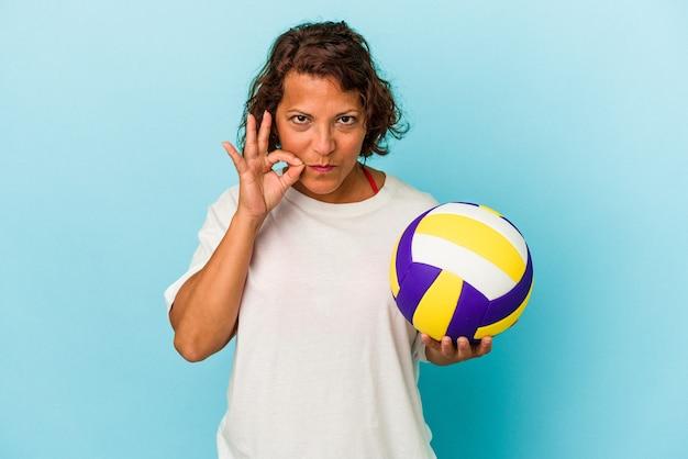 秘密を保持している唇に指で青い背景に分離されたバレーボールをしている中年ラテン女性。