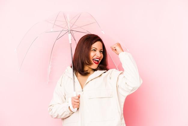 승리, 승자 개념 후 주먹을 제기 절연 우산을 입고 중년 라틴 여자.