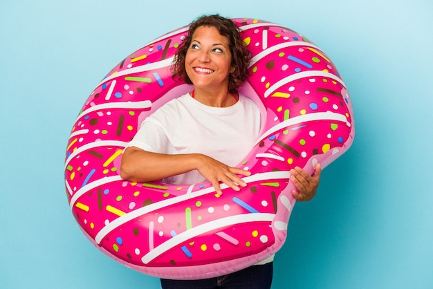 Middle age latin woman with air mattress isolated on white background dreaming of achieving goals and purposes