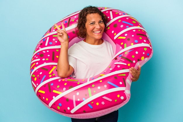 Middle age latin woman with air mattress isolated on white background joyful and carefree showing a peace symbol with fingers.