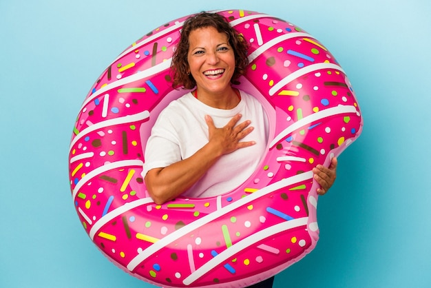 Middle age latin woman with air mattress isolated on white background laughs out loudly keeping hand on chest.