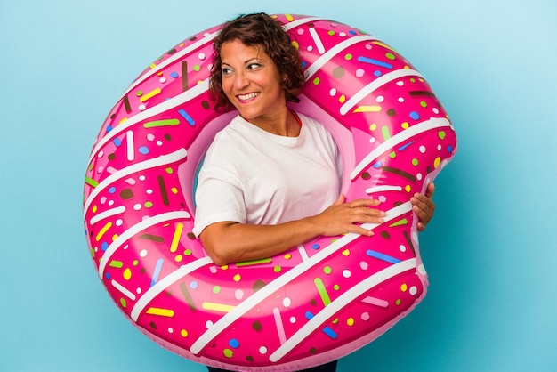 Middle age latin woman with air mattress isolated on white background looks aside smiling, cheerful and pleasant.