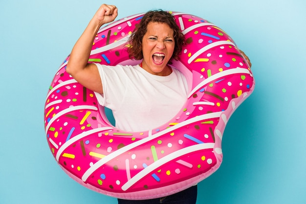 Middle age latin woman with air mattress isolated on white background raising fist after a victory, winner concept.