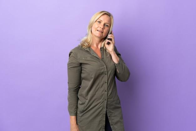 携帯電話との会話を維持している紫色の壁に隔離された中年リトアニアの女性