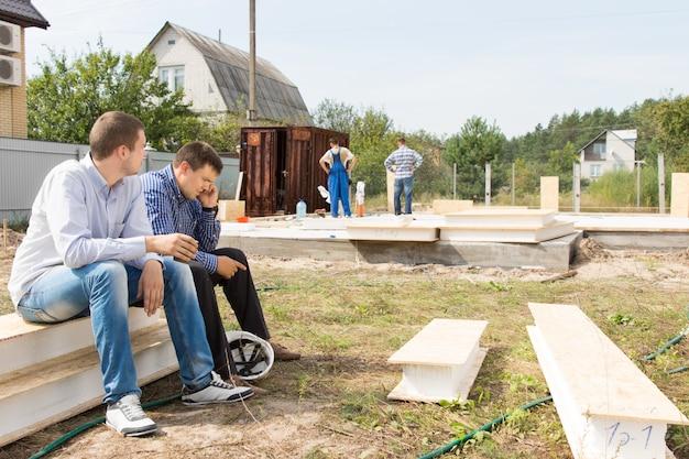 忙しい建設作業員を背景にサイトの近くに座っている中年男性の建築エンジニア