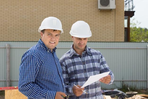 建物の進捗状況を監視するために建設現場を訪問する白いヘルメットを持つ中年男性の建築エンジニア。