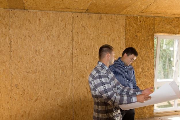 Middle age male engineers reviewing building interior design on blueprint at the site.
