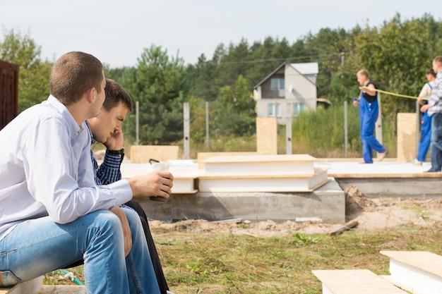 建設作業員を背景にプロジェクトサイトの隅に座っている中年男性エンジニア。
