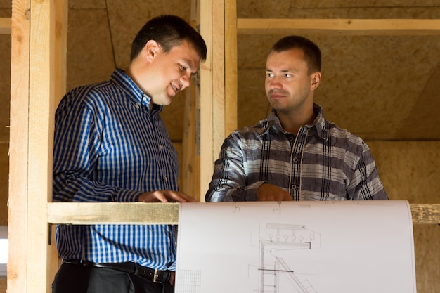 Middle age male professional designers talk about the building designs at the site.