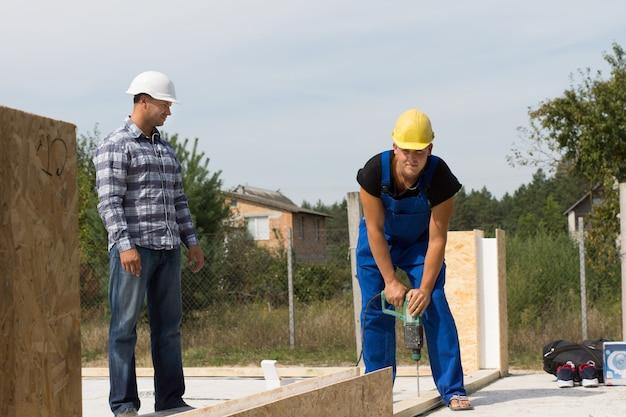 Средний возраст мужской профессиональный инженер, контролирующий строителя во время бурения на строительной площадке.
