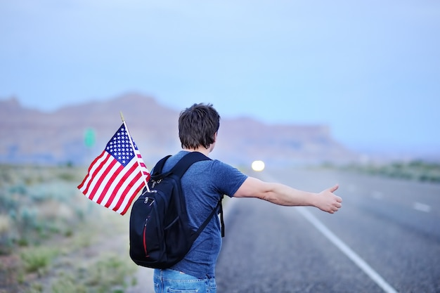 Middle age male tourist with american flag in backpack hitchhiking along a desolate road